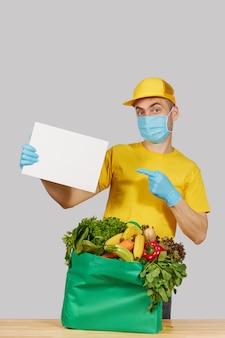 Concetto di shopping online. il corriere maschio in uniforme gialla, maschera protettiva e guanti con un contenitore di drogheria frutta e verdura fresca detiene un banner bianco per il testo. consegna a domicilio di alimenti durante la quarantena