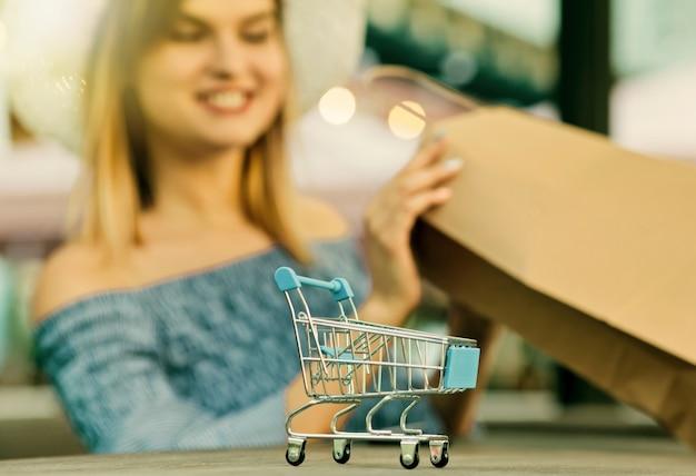 Concetto di acquisto online. mini carrello della spesa primo piano con sfondo sfocato di giovane donna attraente per lo shopping shop