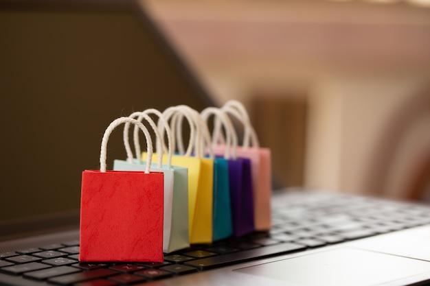 Shopping in linea concetto borse della spesa sulla tastiera del notebook.