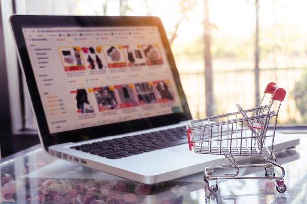 Concetto di shopping online: carrello della spesa o carrello e laptop sul tavolo