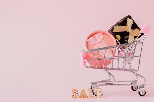 Concetto online di acquisto, carrello con i contenitori di regalo in tavola rosa con lo spazio della copia