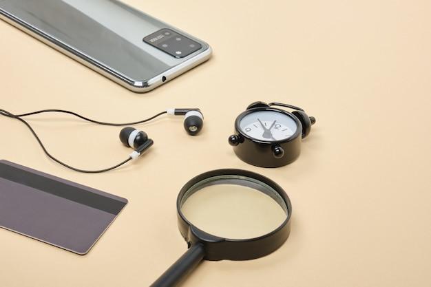 Concetto di acquisto online. smartphone con cuffie per carte di credito, lente d'ingrandimento, sveglia su sfondo beige
