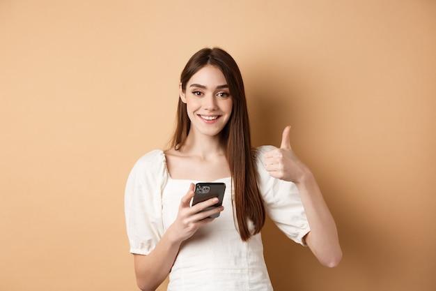 Concetto di shopping online sorridente donna felice che mostra pollice in su dopo aver utilizzato lo smartphone che tiene il telefono e...