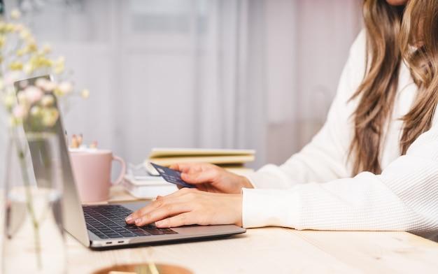 Concetto di acquisto in linea, mani di donna che digitano al computer portatile con carta di credito