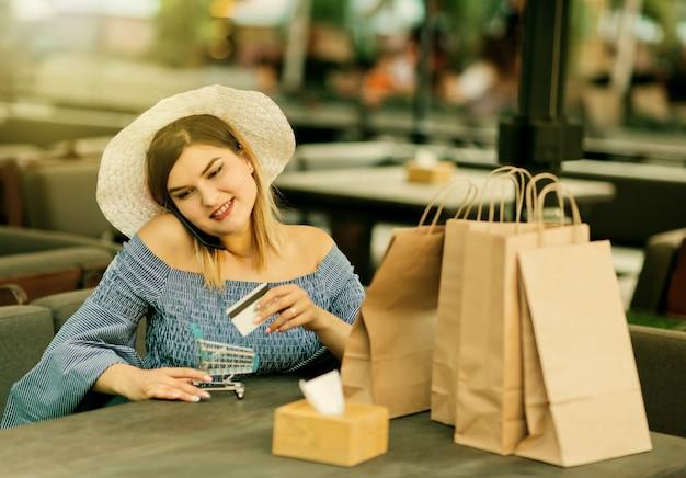 Concetto di acquisto online. giovane donna allegra dello shopping con sacchetti di carta della spesa seduta in un caffè all'aperto e con in mano una carta di credito e un mini carrello della spesa mentre parla al telefono