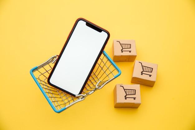 Concetti di acquisto online con cestino, scatole e smartphone su colore giallo