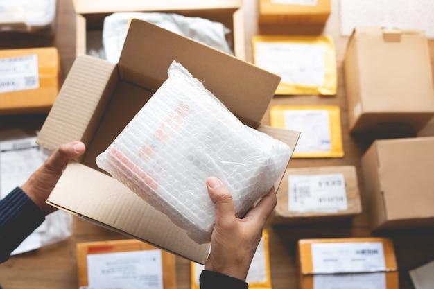 Concetti di acquisto in linea con mano maschio che imballa alcuni prodotti alla scatola marrone