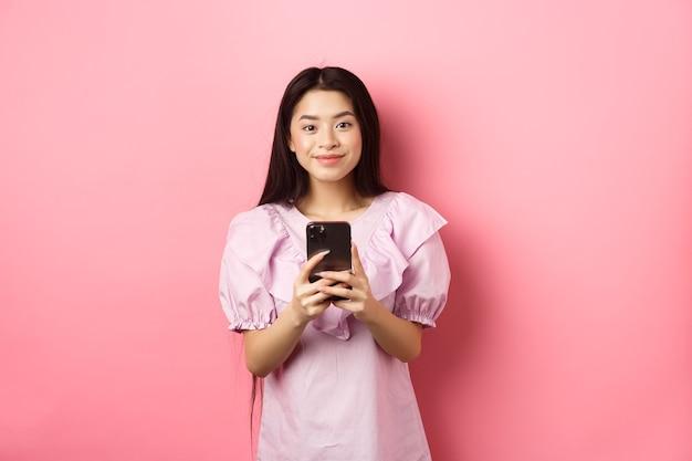 Acquisti online. carina ragazza asiatica sorridente, tenendo il telefono cellulare con la faccia felice, in piedi in abito su sfondo rosa.