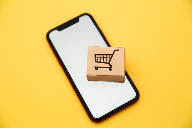 Shopping online ed e-commerce tramite il concetto di internet: scatola e smartphone su sfondo giallo.