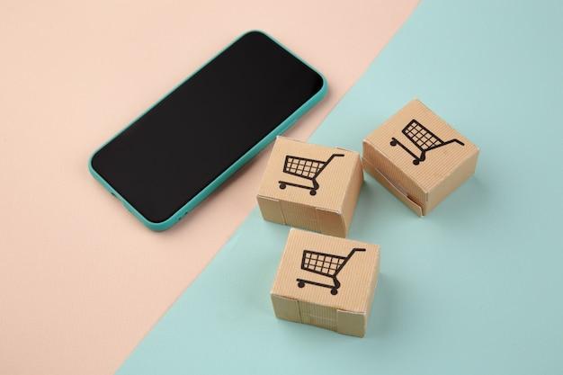 Shopping online ed e-commerce tramite il concetto di internet: scatole accanto a uno smartphone.