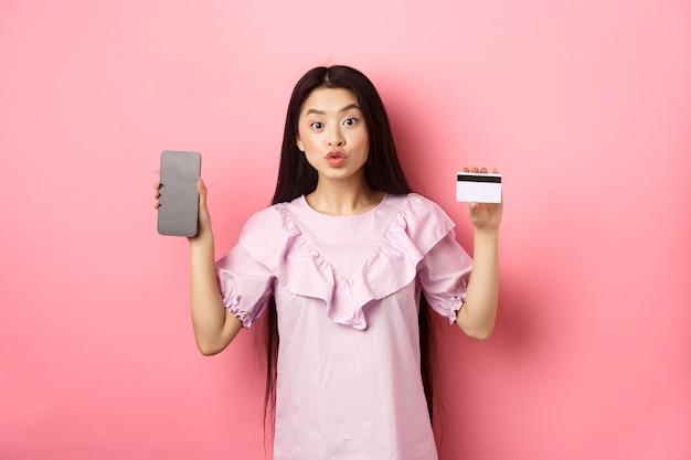 Acquisti online. donna asiatica emozionante che mostra la carta di credito di plastica con lo schermo vuoto dello smartphone, negozio di internet di pubblicità, stante su fondo rosa.