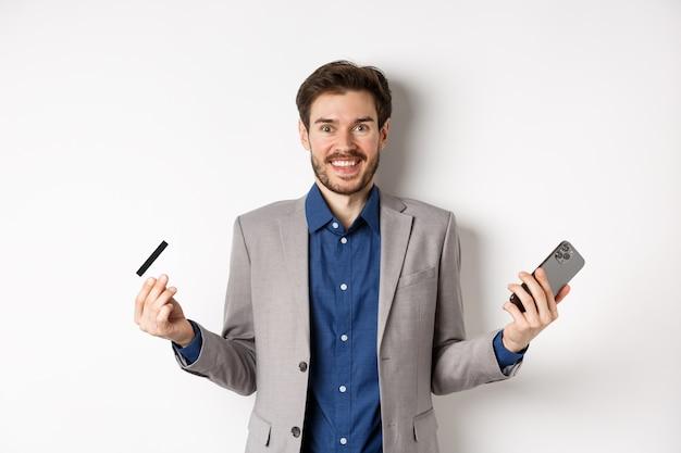 Acquisti online. uomo eccitato che fa soldi, sorridente stupito, che tiene smartphone e carta di credito, in piedi su sfondo bianco in tuta.