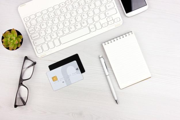 Acquisti online. flatlay con tastiera bianca, carte di credito, occhiali e notebook