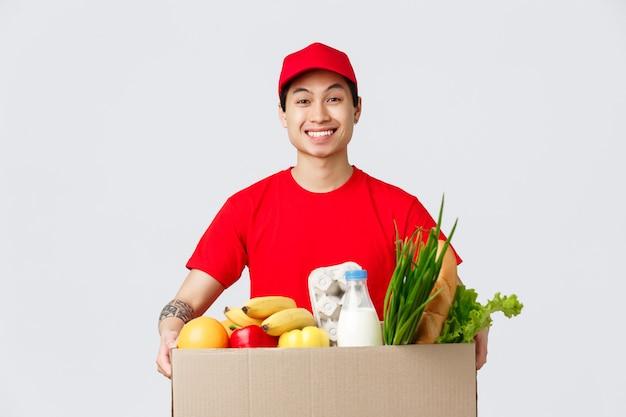 Shopping online, consegna di cibo e concetto di negozi online. ragazzo asiatico sorridente allegro in berretto rosso e maglietta, con scatola con generi alimentari freschi, porta cliente in piedi, dipendente consegna prodotto
