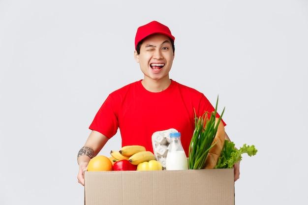 Shopping online, consegna di cibo e concetto di negozi online. corriere asiatico sorridente amichevole in berretto rosso e maglietta, in possesso di pacchetto con consegna di generi alimentari, strizza l'occhio al cliente, offre pacchetti di prodotti al cliente