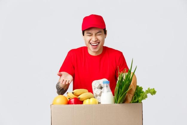 Shopping online, consegna di cibo e concetto di negozi online. bel corriere maschio asiatico in uniforme rossa, ridendo mentre scherza con i dipendenti, consegna pacchi di generi alimentari all'ordine effettuato dal cliente.