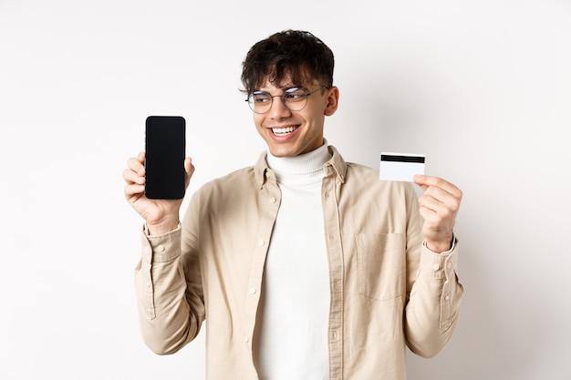 Shopping online bel ragazzo con gli occhiali che mostra lo schermo del cellulare vuoto e la carta di credito che sorri...