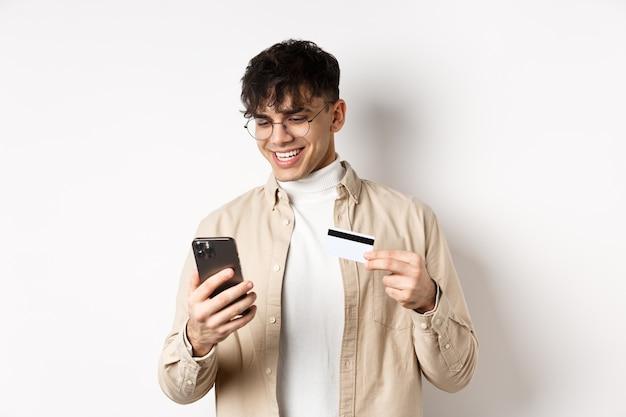 Acquisti online. giovane felice che utilizza smartphone e carta di credito in plastica, pagando in internet, in piedi sul muro bianco.