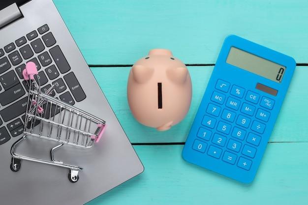 Idee per lo shopping online. computer portatile con salvadanaio, carrello del supermercato, calcolatrice su una superficie di legno blu. concetto di risparmio. vista dall'alto