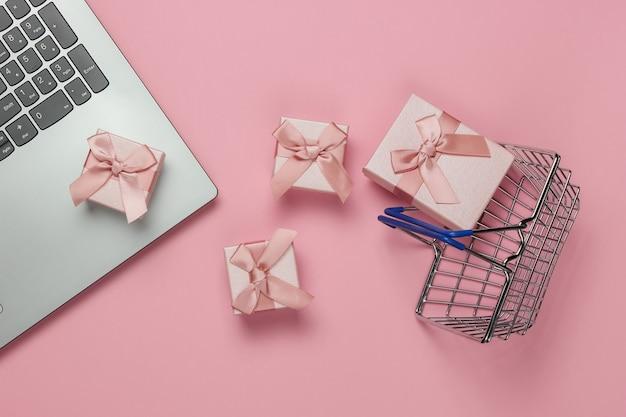 Acquisti online. computer portatile, cestino della spesa e scatole regalo con fiocchi su sfondo rosa pastello. composizione per natale, compleanno o matrimonio. vista dall'alto