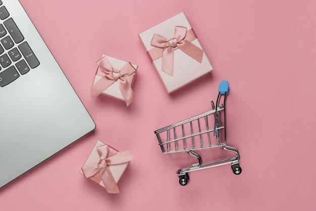 Acquisti online. computer portatile, carrello della spesa e scatole regalo con fiocchi su sfondo rosa pastello. composizione per natale, compleanno o matrimonio. vista dall'alto