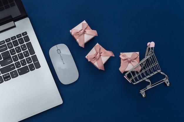 Acquisti online. computer portatile con mouse per pc, carrello della spesa con scatole regalo su sfondo blu classico. colore 2020. vista dall'alto.
