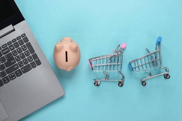 Acquisti online. computer portatile con salvadanaio, carrello del supermercato su pastello blu