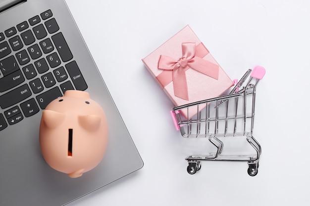 Acquisti online. computer portatile con salvadanaio, carrello del supermercato, confezione regalo su bianco
