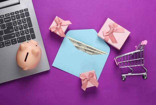 Acquisti online. computer portatile con salvadanaio, carrello del supermercato, scatole regalo, busta con dollari in viola