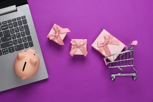 Acquisti online. computer portatile con salvadanaio, carrello del supermercato, scatole regalo su viola