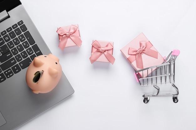 Acquisti online. computer portatile con salvadanaio, carrello del supermercato, scatole regalo su bianco