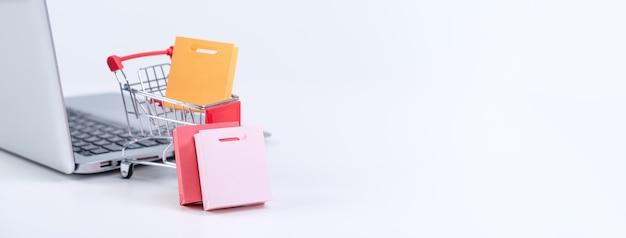Acquisti online. mini carrello del carrello del negozio con sacchetti di carta colorati su un computer portatile su sfondo bianco da tavola, acquisto a casa concetto, primi piani