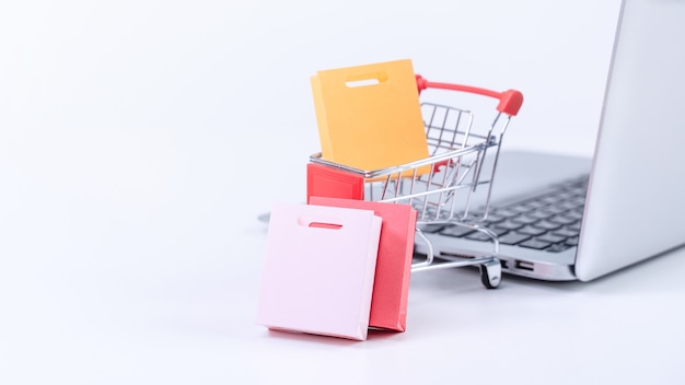 Acquisti online. carrello del mini negozio con sacchetti di carta colorati su un computer portatile su sfondo bianco del tavolo, concetto di acquisto a casa, primo piano