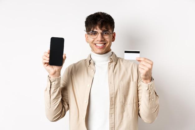 Acquisti online. ragazzo naturale con gli occhiali che mostra lo schermo vuoto dello smartphone e la carta di credito in plastica, sorridendo soddisfatto, raccomandando la banca, in piedi sul muro bianco.