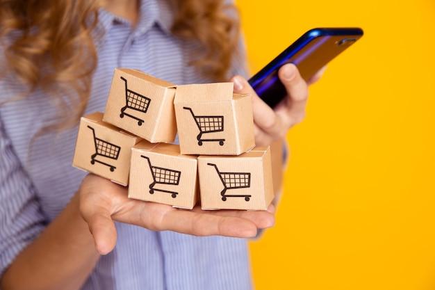 Acquisti online. scatole di carta in mano e telefono della donna. concetto di servizio di consegna.