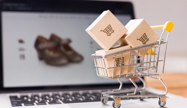 Acquisti in linea: cartoni o pacchi di carta con il logo di un carrello della spesa e un piccolo carrello sulla tastiera di un laptop che il negozio online acquista sullo schermo, servizio di acquisto sul web in linea e offre la consegna a domicilio.