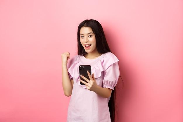 Acquisti online. ragazza asiatica soddisfatta che vince sul telefono cellulare, dice di sì e fa la pompa del pugno, tenendo lo smartphone, in piedi su sfondo rosa.