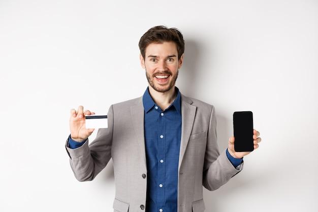 Acquisti online. uomo d'affari sorridente in tuta che mostra la carta di credito in plastica con lo schermo vuoto dello smartphone, in piedi su sfondo bianco.