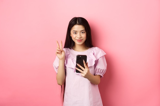 Acquisti online. elegante ragazza adolescente asiatica utilizza lo smartphone, mostra il segno di pace e sorride soddisfatto della fotocamera, in piedi su sfondo rosa.