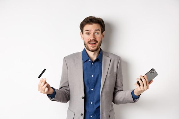Acquisti online. imprenditore sorpreso in possesso di carta di credito in plastica e smartphone, fare soldi in internet, in piedi in tuta su sfondo bianco.