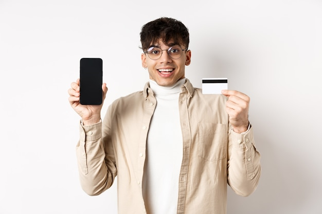 Acquisti online. giovane sorpreso e felice che mostra la carta di credito e lo schermo del telefono cellulare, in piedi sul muro bianco.