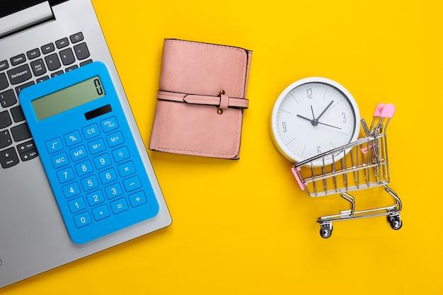 Online, tempo per lo shopping. mini carrello del supermercato con orologio, portafoglio, laptop, calcolatrice su una superficie gialla. vista dall'alto. lay piatto
