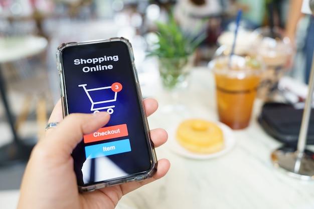 Shopping online con servizio di consegna smartphone e borse della spesa utilizzando come shopping di sfondo