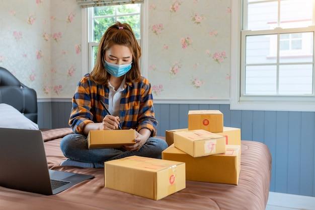 Le giovani donne dello shopping online iniziano una piccola impresa in una scatola di cartone al lavoro.