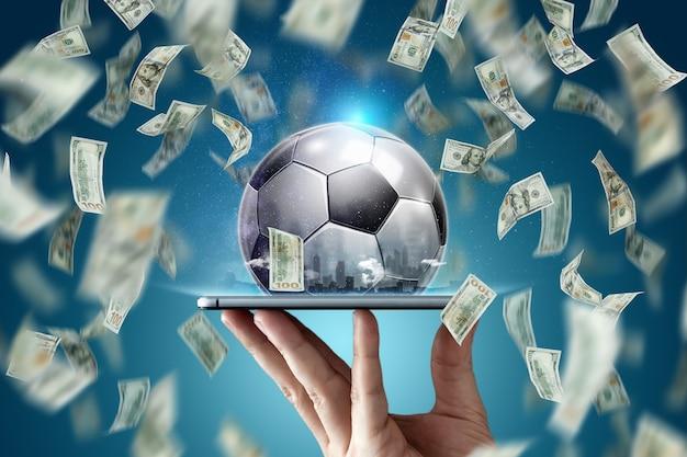 Scommesse sportive online. i dollari cadono sullo sfondo di una mano con uno smartphone e un pallone da calcio. background creativo, gioco d'azzardo.