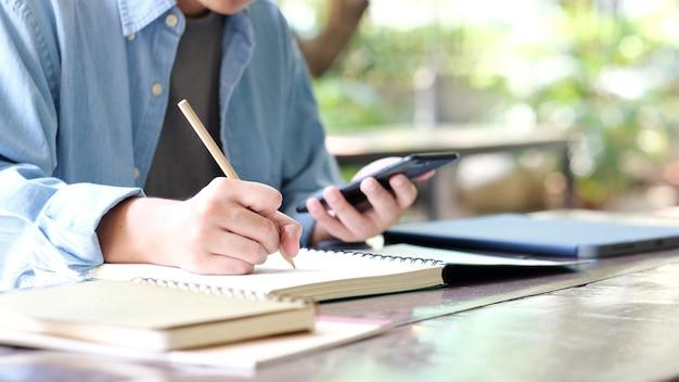 Studio online studente che scrive a mano sul taccuino durante l'utilizzo del telefono cellulare