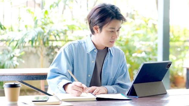 Lezione di studio online studente che scrive a mano sul taccuino durante l'utilizzo della tavoletta digitale