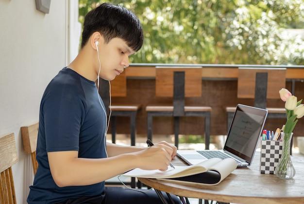 Concetto di studio online uno studente dai capelli neri che fa i compiti cercando informazioni su internet e usando questa penna nera per scrivere la conclusione della sua ricerca sulla carta.