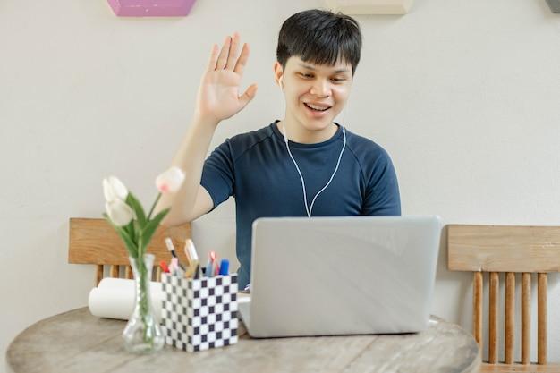 Concetto di studio online uno studente maschio che studia dall'aula online usando il suo nuovo laptop bianco alzando la mano sinistra per fare alcune domande all'insegnante.