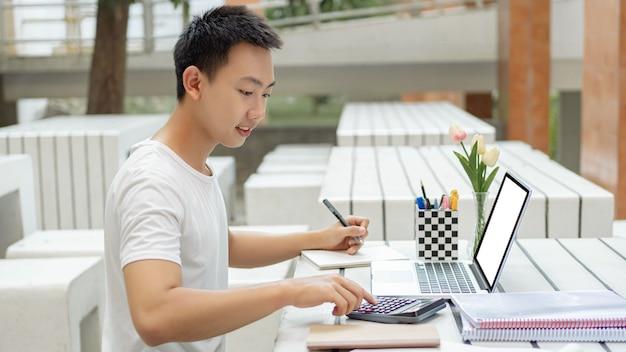 Concetto di studio online uno studente maschio in maglietta bianca che studia online usando il suo nuovo laptop bianco e la calcolatrice nella classe di contabilità.